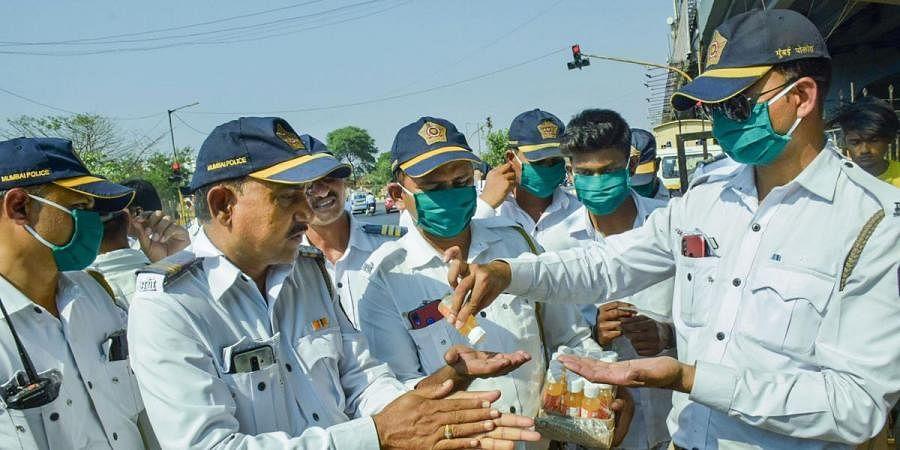 Traffic police personnel sanitize their hands in the wake of deadly coronavirus at Vikhroli in Mumbai