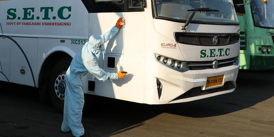 A worker sprays disinfectant on a SETC bus amid concerns over the spread of novel coronavirus at Koyembedu bus depot in Chennai