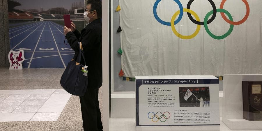 A man wearing a mask takes pictures of the mascots for the Tokyo 2020 Olympics and Paralympics in Tokyo. (Photo | AP)