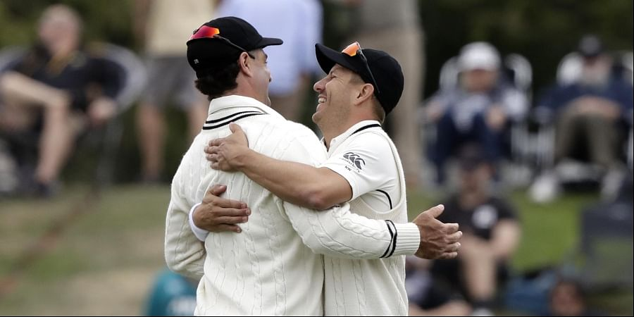 New Zealand's Neil Wagner, right, and Colin de Grandhomme embrace as they leave the field after India was dismissed for 124 runs. (Photo  AP)