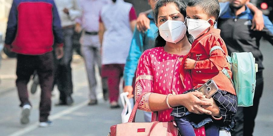 A mother and child wearing protective masks in the wake of COVID-19 outbreak, at Safdarjung Hospital on Wednesday