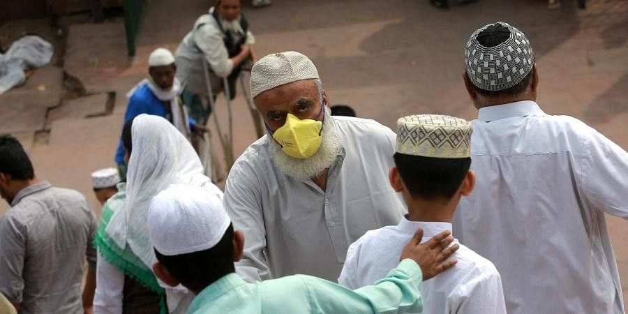 People, wearing facemasks amid concerns over the spread of the COVID-19, visit the Jama Masjid mosque in New Delhi