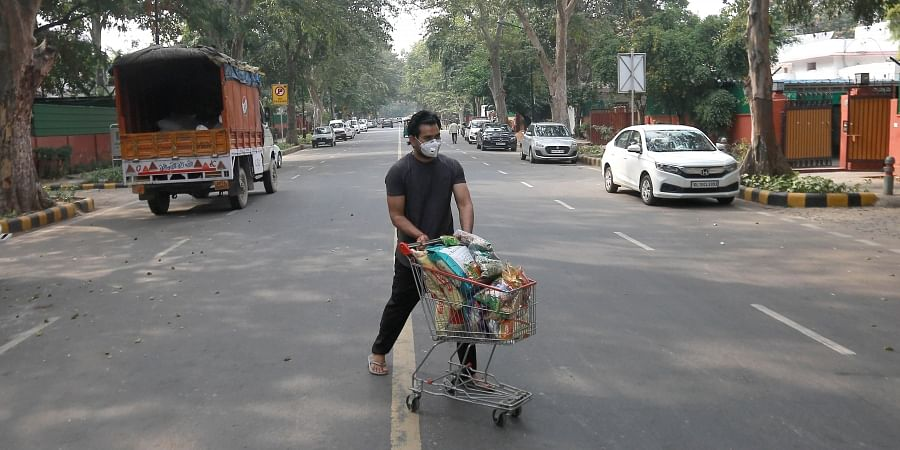 A man wearing mask wheels essential goods across a deserted road in New Delhi on Friday due to coronavirus.