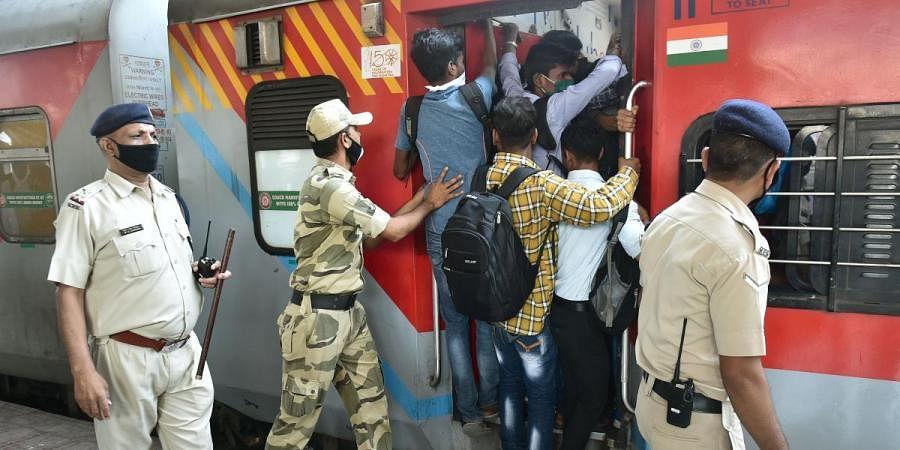 Passengers board a crowded train amid coronavirus scare in Thane on Saturday