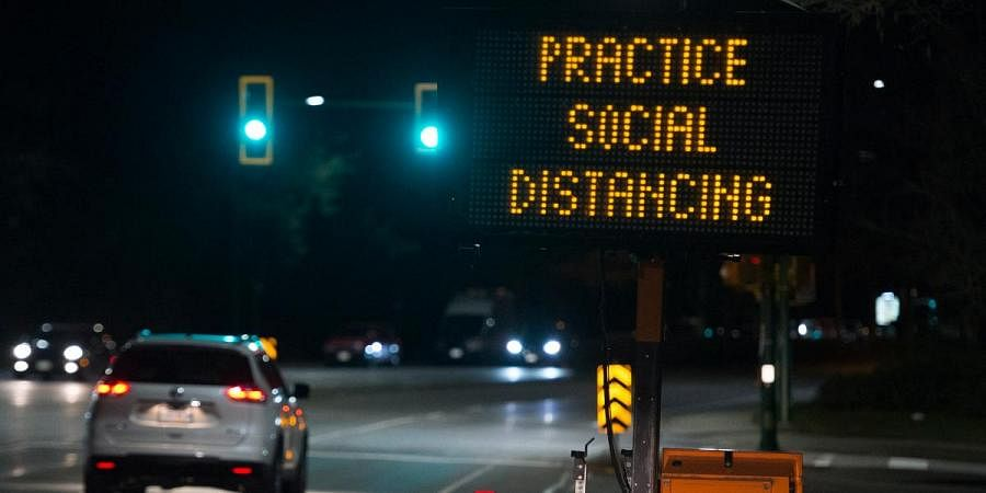 A sign reminding people about 'social distancing' in the midst of the coronavirus outbreak stands next to a roadway in North Vancouver, British Columbia, Canada