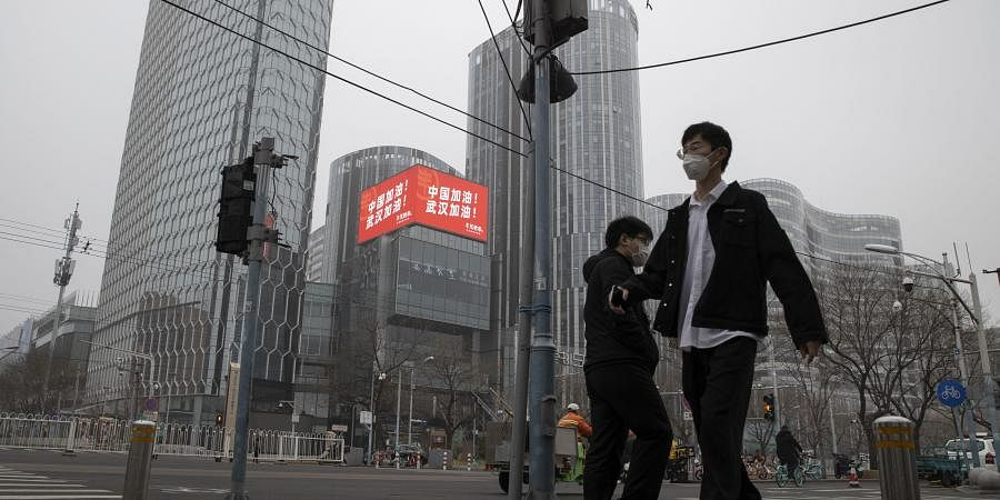 Residents walk past a retail and office district with a screen showing propaganda which reads 'Go China! Go Wuhan' as businesses slowly restart in Beijing on Sunday, March 8, 2020.