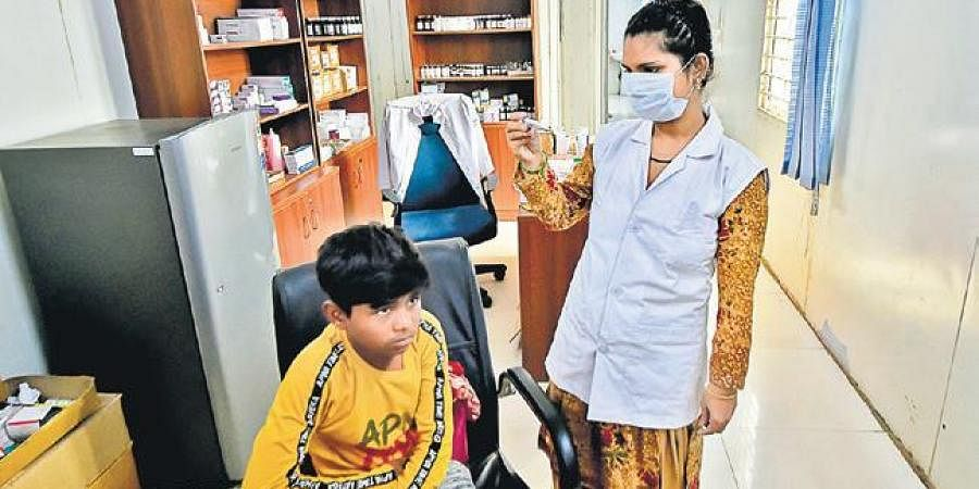 A boy being tested by a nurse at a Mohalla clinic on Saturday (Photo | PTI)