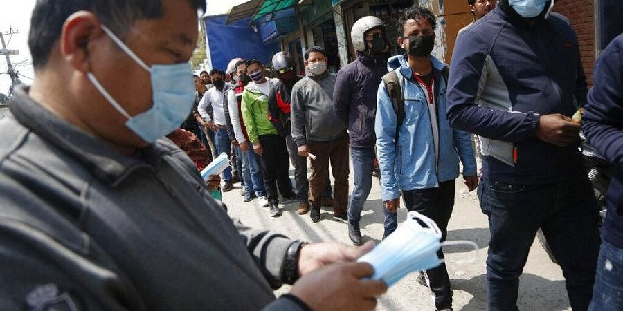 Nepalese men line up outside a pharmacy to buy face masks which are in high demand due to COVID-19 situation in Kathmandu, Nepal, Friday, March 20, 2020.