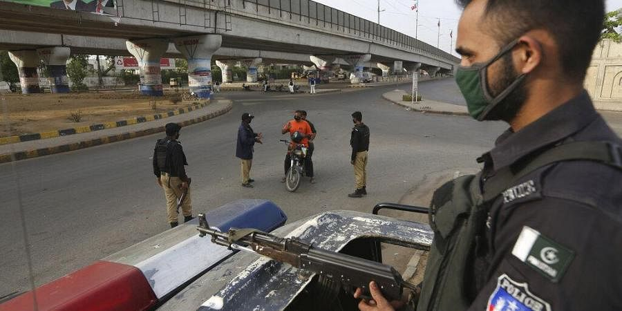Pakistani police officers stop travelers after a government announced to lockdown the city due to concerns over the spread of the new coronavirus, in Karachi, Pakistan, Monday, March 23, 2020.