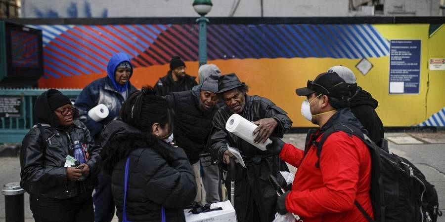 elix Guzman, right, and his wife Virna wear protective gloves and masks due to COVID-19 concerns as they hand out disposable gloves and sanitizing wipes to a group of people who are homeless on 34th Street, Saturday, March 21, 2020, in New York.