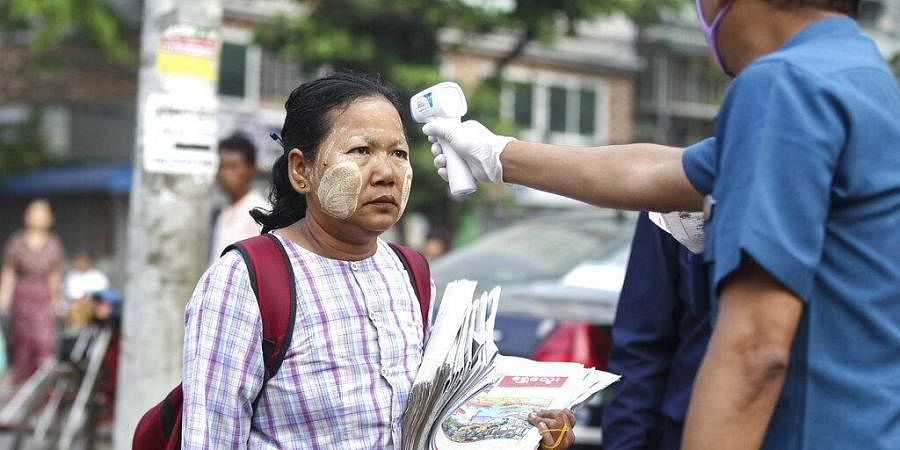 A journal vendor is measured the body temperature by a member of Yangon City Development Committee during a public awareness for prevention of the novel coronavirus at a market in Yangon, Myanmar