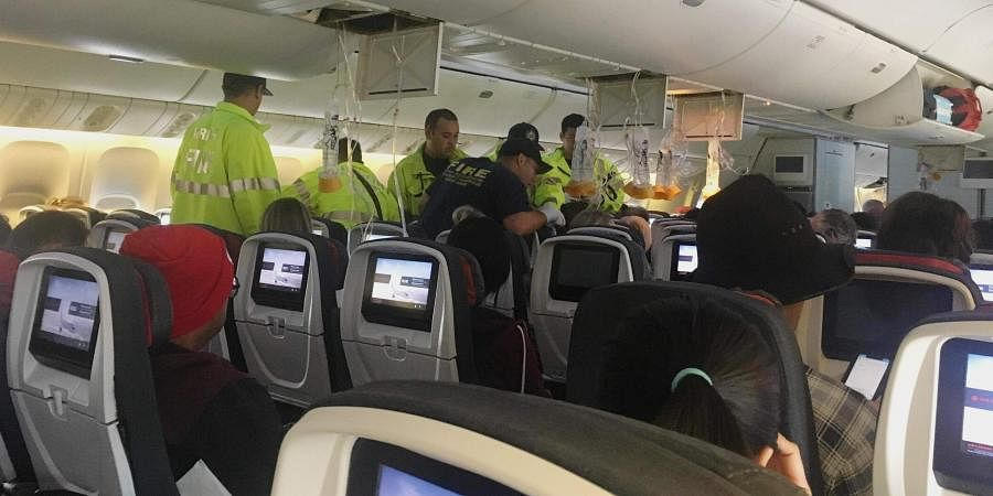 Responders treat a passenger on an Air Canada flight to Australia that was diverted and landed at Daniel K. Inouye International Airport in Honolulu on July 11, 2019. (Photo | AP)