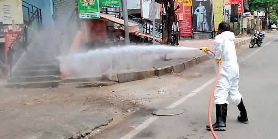 A GHMC worker spraying disinfectants on a road in Hyderabad on Monday