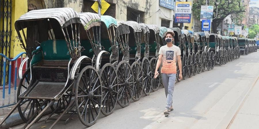 A boy wearing a mask walks past parked rickshaws alongside a street during lockdown in the wake of coronavirus outbreak, in Kolkata