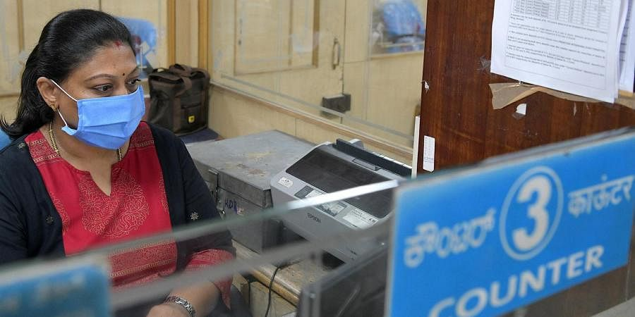 A bank employee taking precautionary measure by using mask in Bengaluru