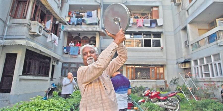 People come out to clap, clang utensils at an apartment to cheer health workers.