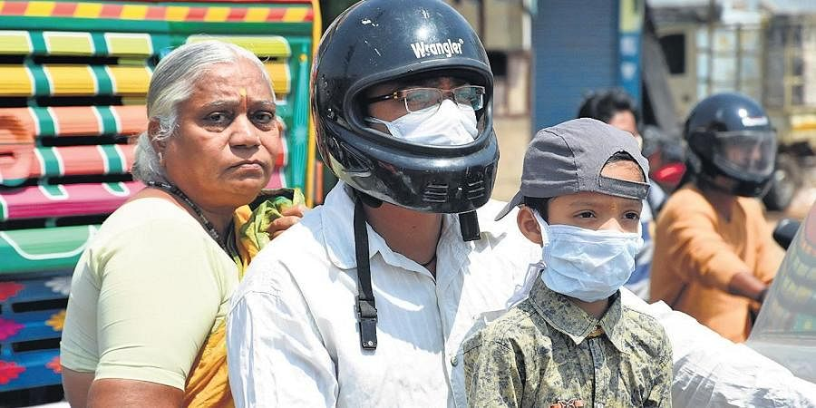 A father and his son wear masks, while the elderly woman doesn't have one as they go on a bike