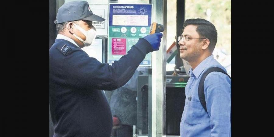 A security guard runs a check on the body temperature of a visitor to an office in New Delhi on Monday