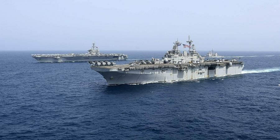 The amphibious assault ship USS Kearsarge sails in front of the USS Abraham Lincoln aircraft carrier in the Arabian Sea. Commercial airliners flying over the Persian Gulf risk being targeted by 'miscalculation or misidentification' from the Iranian military amid heightened tensions between the Islamic Republic and the US