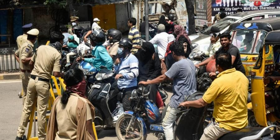 Police block a street, allowing only those who are travelling to get essential commodities to pass through, during the lockdown in Hyderabad