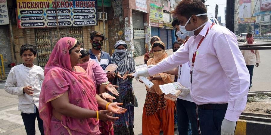 Social activists hand sanitize people, who came out to buy the essentials during the lockdown throughout the country, to contain the spread of coronavirus in Patna