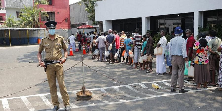 Sri Lankans queue for kerosene as a police officer stands guard during a temporary lift of a curfew as virus-containment measures in Colombo, Sri Lanka, Tuesday, March 24, 2020.