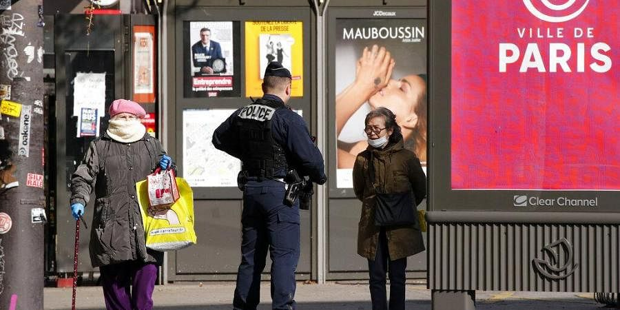 French police officer controls passers by in Paris. (Photo   AP)