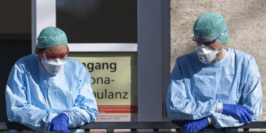 Employees of the Corona Outpatient Clinic at the University Hospital stand in protective clothing and breathing masks in front of the entrance, Dresden, Germany