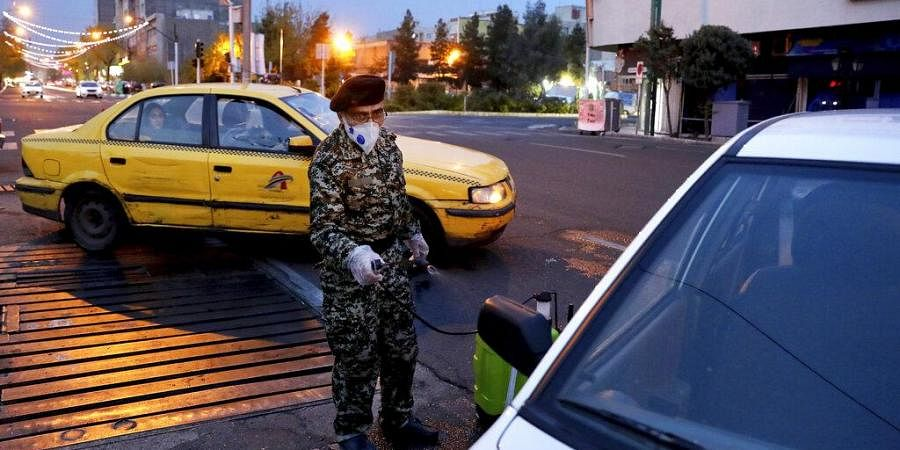 A Revolutionary Guard member disinfects a car to help prevent the spread of the new coronavirus in downtown Tehran, Iran. (Photo | AP)