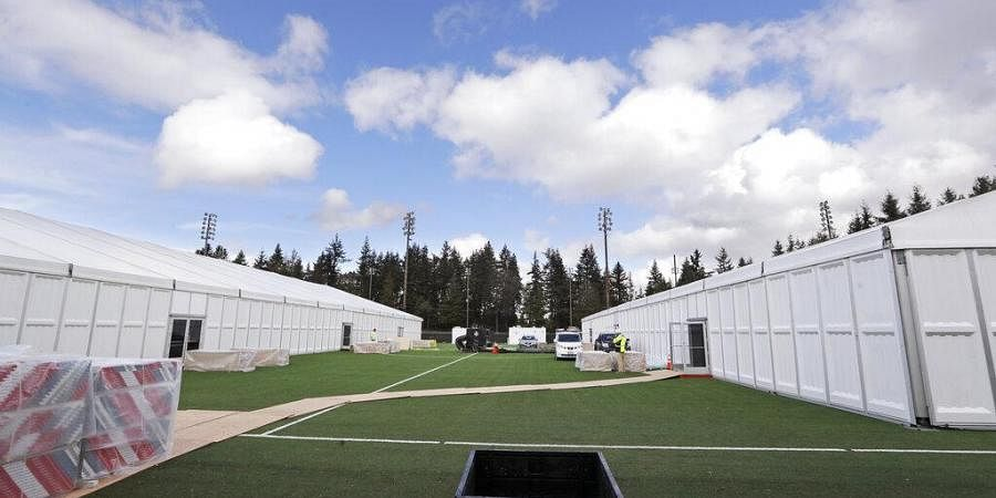In this photo taken Tuesday, March 24, 2020, two massive temporary buildings meant for use as a field hospital for coronavirus patients stand together on a soccer field in the Seattle suburb of Shoreline, Wash.