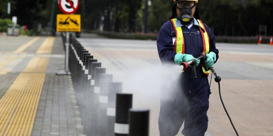 A worker sprays disinfectant at the pedestrian walkway at Senayan Sports Complex amid coronavirus outbreak, in Jakarta, Indonesia. (Photo | AP)