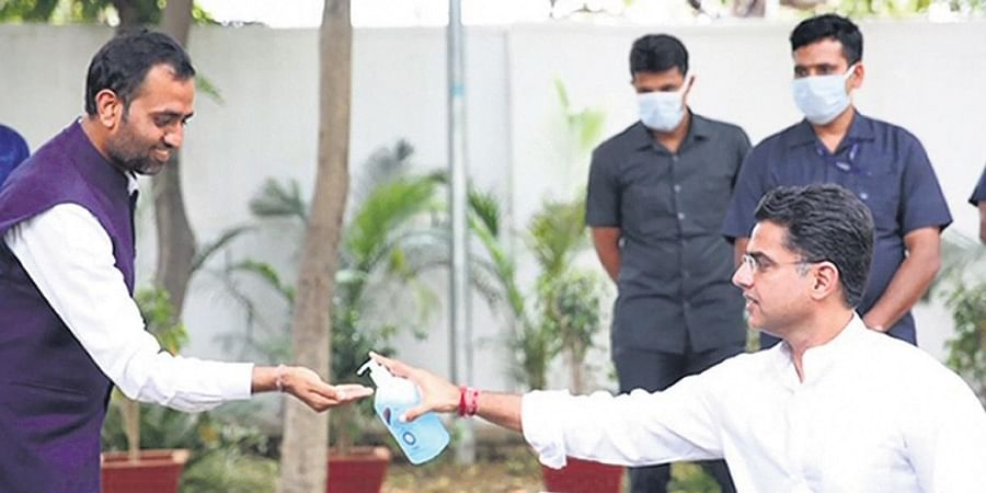Deputy CM Sachin Pilot offers a sanitizer solution before a press conference