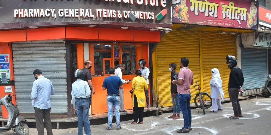 People maintain social distance as they stand outside a chemist shop in Moradabad. (Photo| PTI)