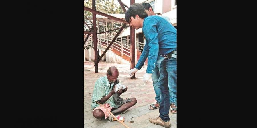 Youths distributing food to a homeless man in Sambalpur