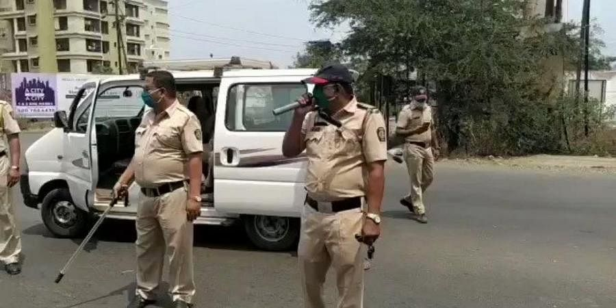 A policeman in Pune raises awarenes of social distancing by a song