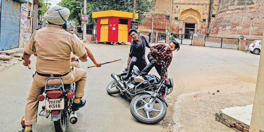 Police personnel charge at a biker for flouting lockdown guidelines, imposed in the wake of coronavirus pandemic, near Razia Sultana Fort in Bathinda, Punjab