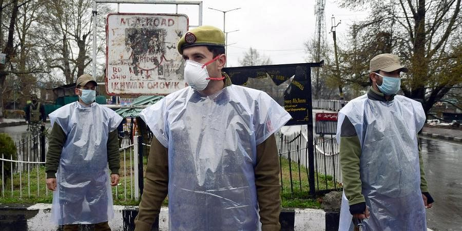 Jammu and Kashmir police personnel wear protective mask during the nationwide lockdown, in wake of COVID-19 in Srinagar