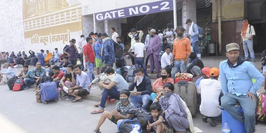 Migrants being transported to their districts and some others waiting outside the rly station for transport in Patna.