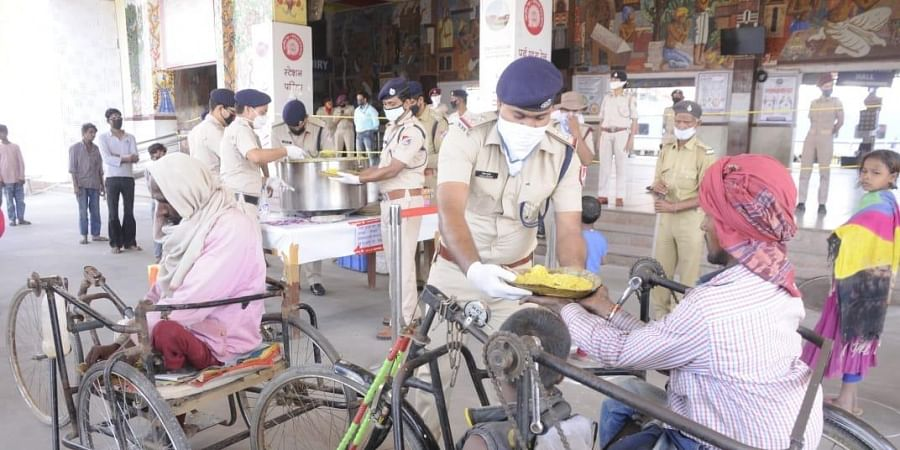 RPF personnels distribute food among the poor, homeless people near Patna junction. (Photo | Ranjit K Dey, EPS)