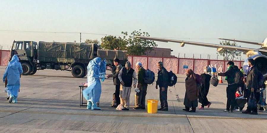 Medics screen passengers, who were airlifted from Iran, before being sent for a mandatory isolation period to an Indian Army Wellness Facility in Jodhpur