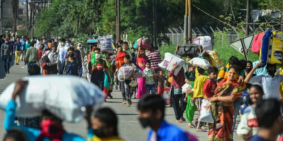 Migrant workers along with their family members walk to their villages, amid a nationwide lockdown in wake of coronavirus pandemic, at Lal Quarter Bus Stand in New Delhi