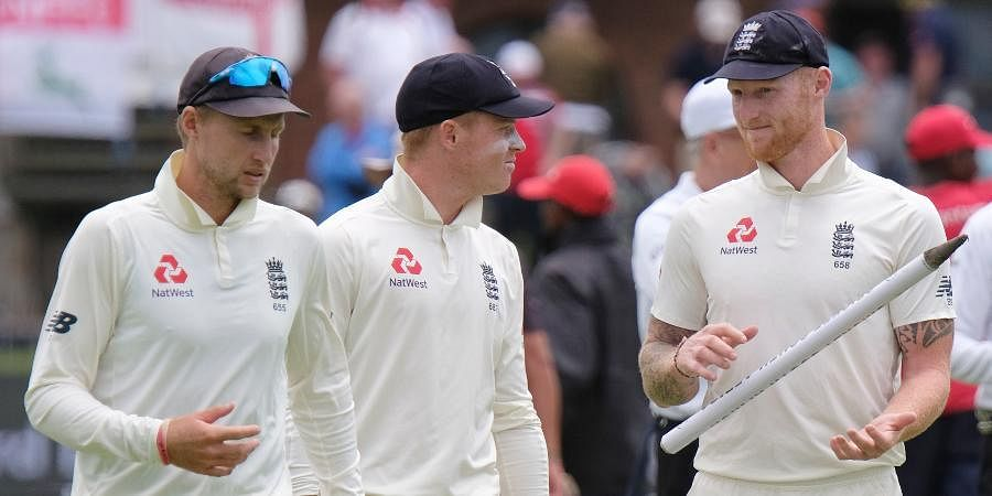 England's captain Joe Root, left, Ollie Pope and Ben Stokes, right, leave the field of play after winning the third cricket test between South Africa and England in Port Elizabeth.