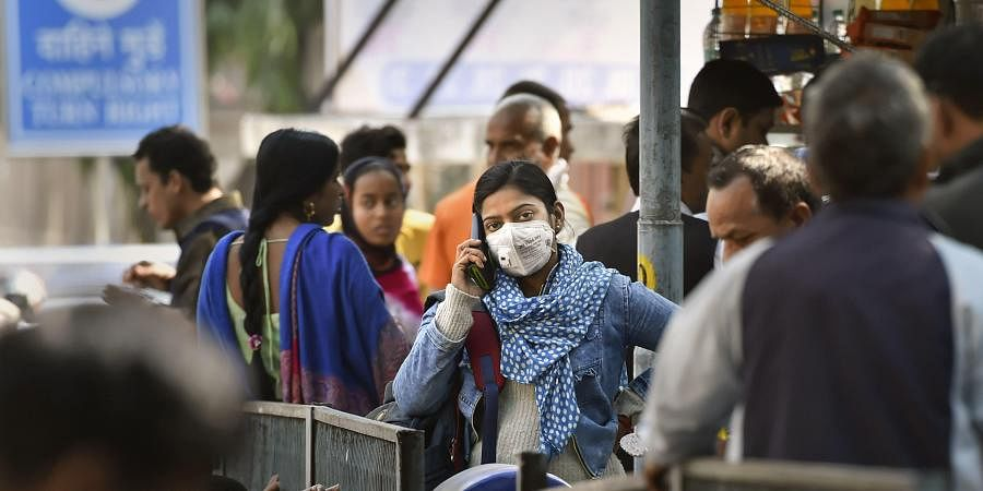 A young woman wearing a protective mask in the wake of novel coronavirus or COVID-19 outbreak speaks on the phone at RML Hospital in New Delhi. (Photo | PTI)