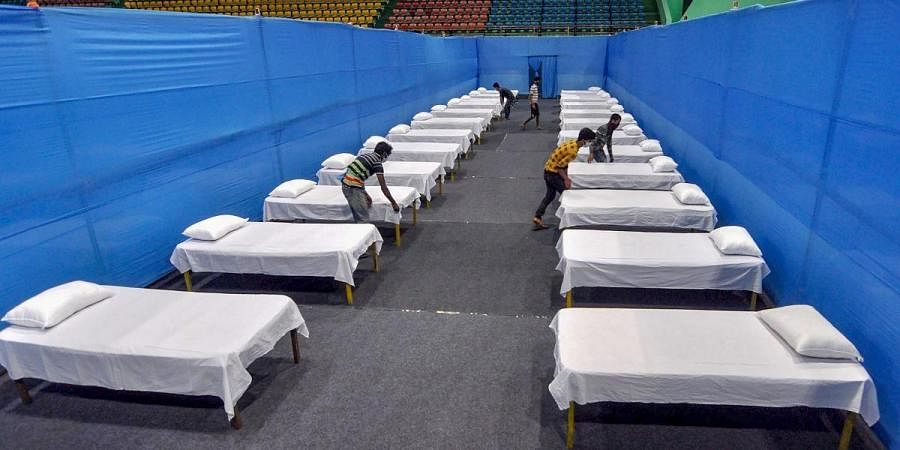 Workers prepare beds inside a quarantine facility for COVID-19 patients, during a nationwide lockdown in the wake of coronavirus pandemic, in Guwahati
