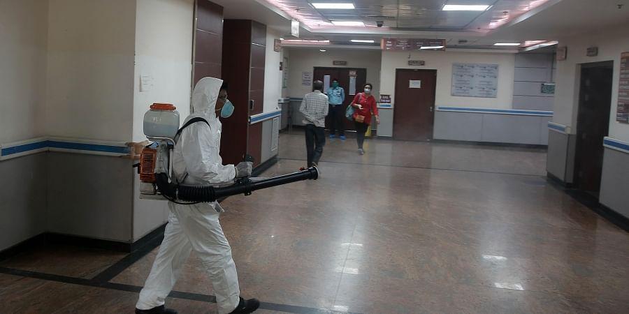 A worker sprays disinfectants in Safdarjung Hospital in Delhi