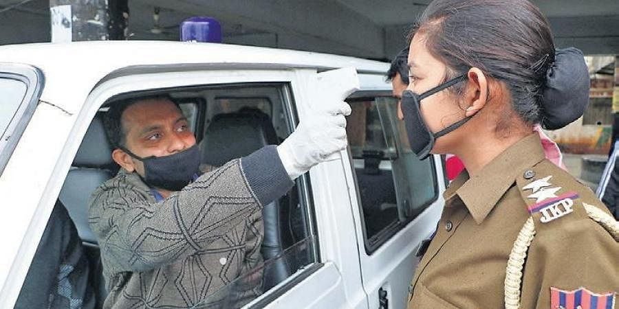 A doctor checks the temperature of a police officer on duty in Jammu. The shortage of PPEs for doctors and healthcare professionals in the country has sparked concerns