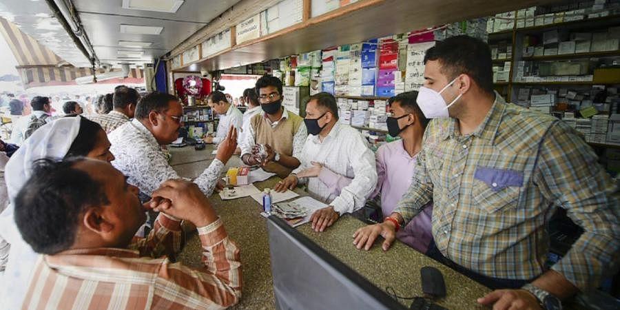 Salesmen at a chemist shop wear protective masks in wake of coronavirus outside Safdarjung Hospital in New Delhi