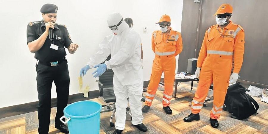 AAI and NDRF teams demonstrate handling of a passenger with suspected symptoms of coronavirus at Vijayawada airport on Thursday