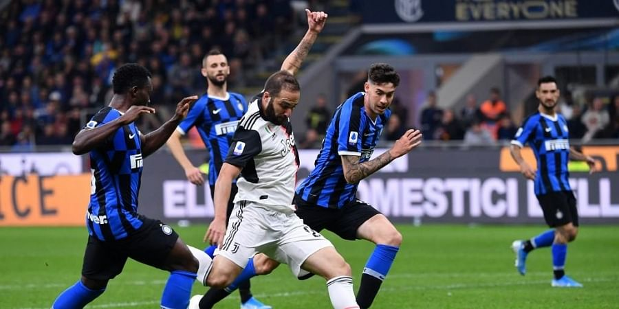Juventus' Argentinian forward Gonzalo Higuain (C) shoots to score during the Italian Serie A football match Inter vs Juventus. (Photo   AFP)
