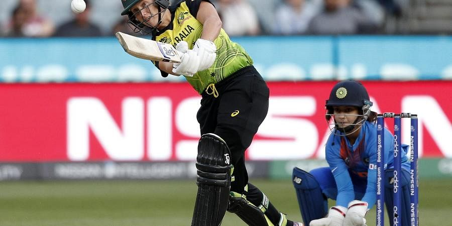 Australia's Alyssa Healy, left, drives the ball in front of IndiaÅfs Tanya Bhatia during the WomenÅfs T20 World Cup cricket final match against India in Melbourne, Sunday, March 8, 2020.